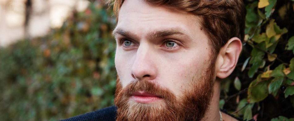 Portrait eines Mannes mit Bart, der hoffnungsvoll dreinschaut, weil er ein berufliches Coaching begonnen hat.