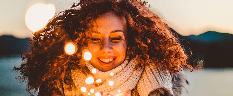 Frau mit glücklichem Gesicht, Lichter in den Händen haltend.